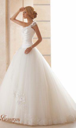 Свадебное платье с асимметричным лифом и многослойным подолом.