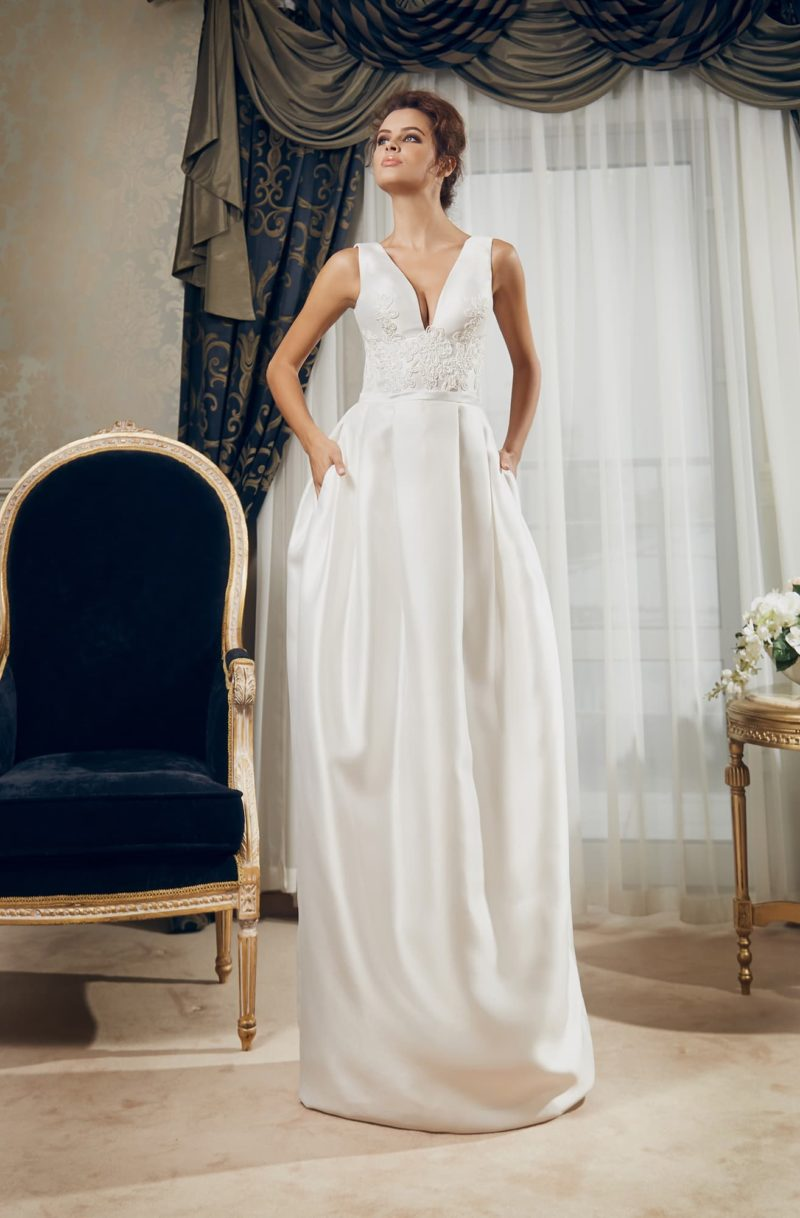 Атласное свадебное платье с глубоким V-образным декольте и оригинальной юбкой с карманами.