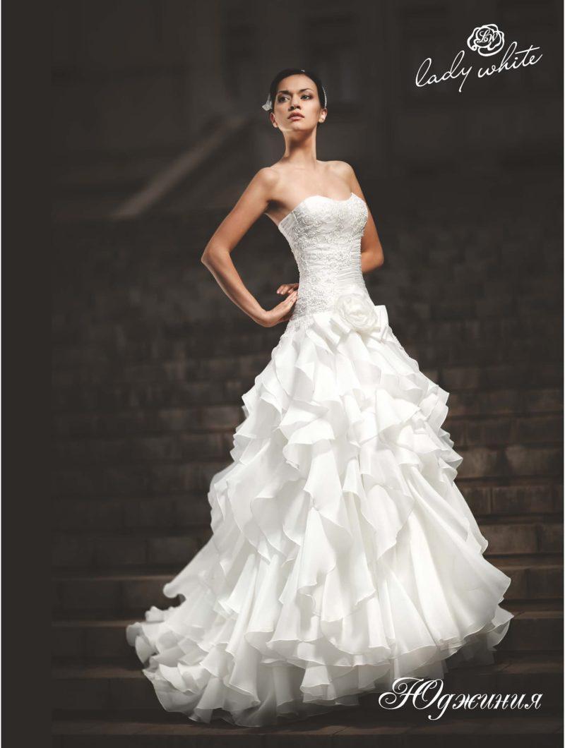 Пышное свадебное платье с открытым лифом и оборками по подолу.