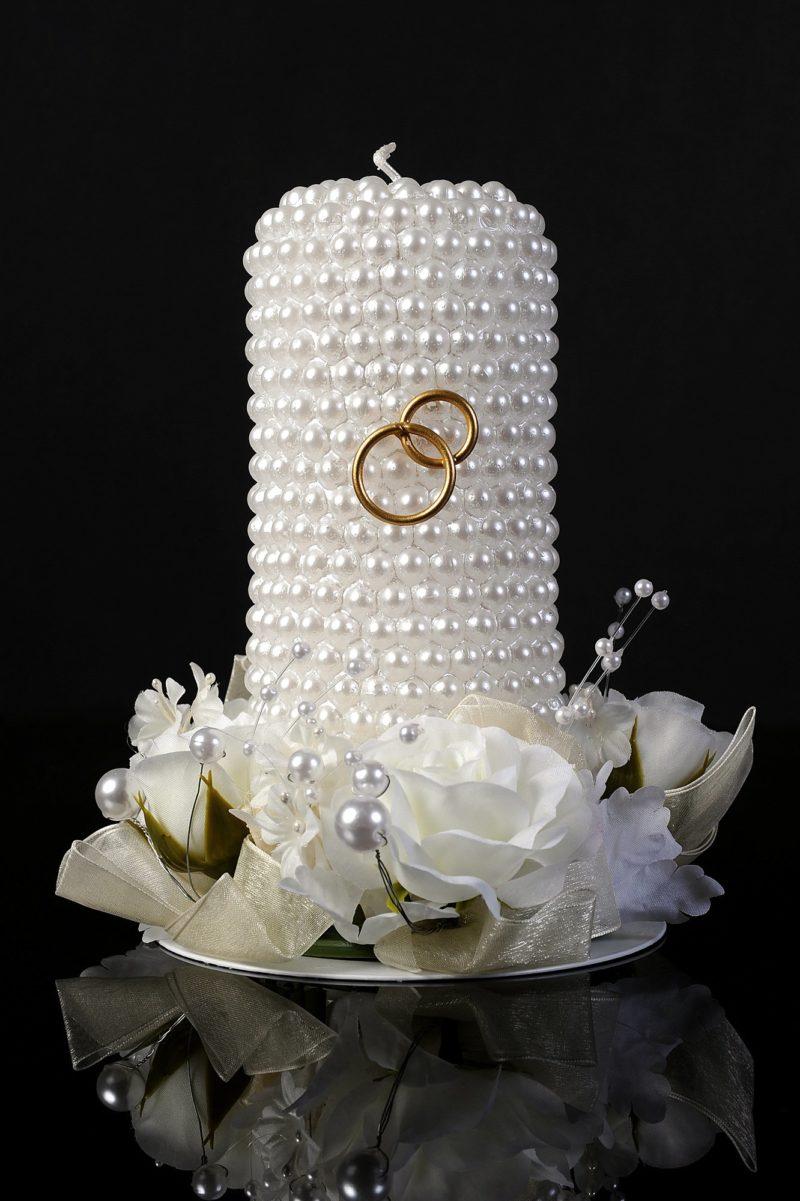 Сияющая свадебная свеча, покрыта декором из перламутровых бусин и золотых колец.