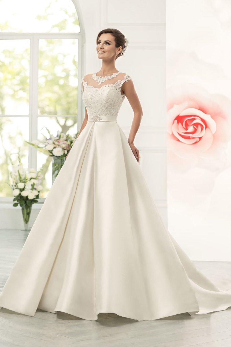 Изысканное свадебное платье с пышной атласной юбкой, узким поясом и лифом, покрытым кружевом.