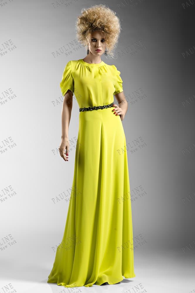 Закрытое вечернее платье желтого цвета с сияющим черным поясом.