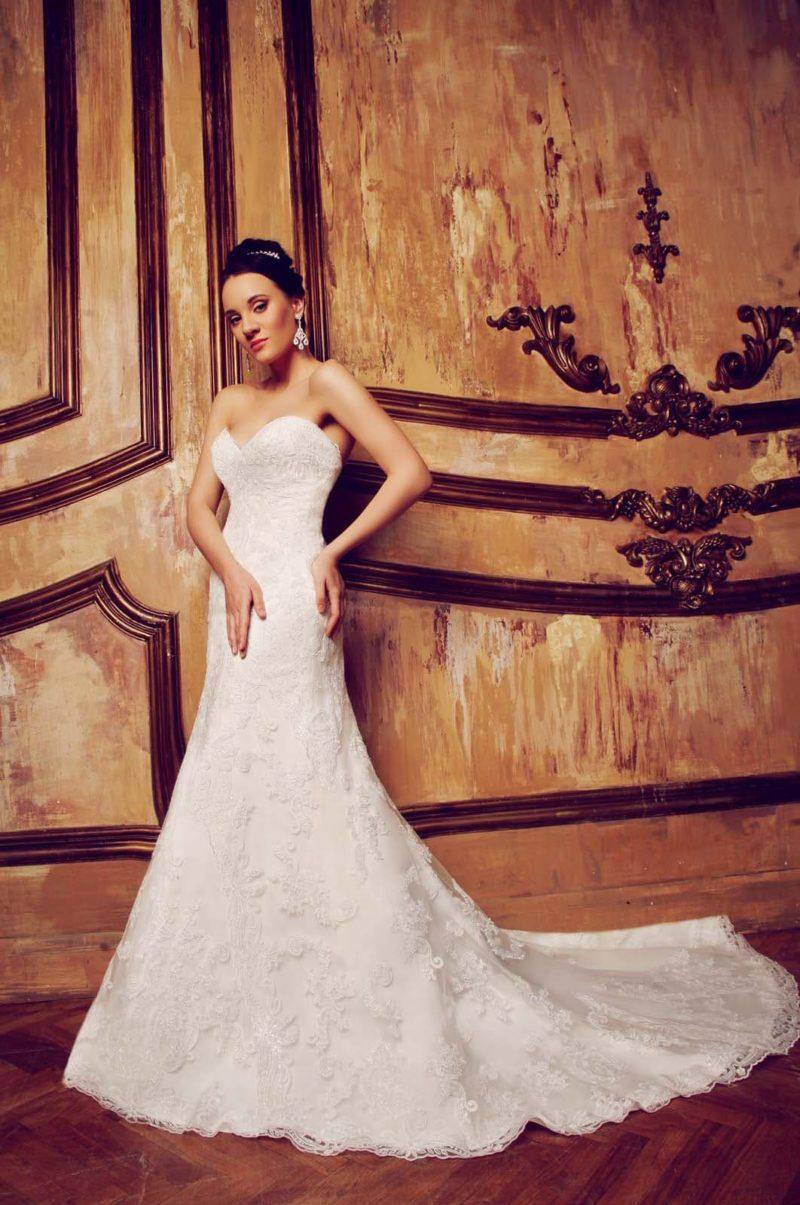 Торжественное свадебное платье с открытым декольте, покрытое по всей длине кружевом.