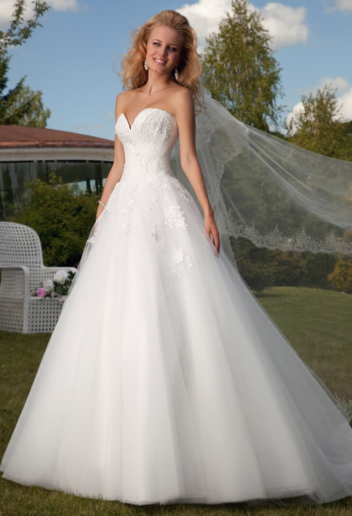 Очаровательное свадебное платье с пышной юбкой и изящным открытым лифом.