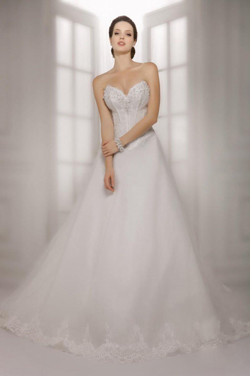 Деликатное свадебное платье с открытым корсетом и нежной многослойной юбкой с пышным шлейфом.