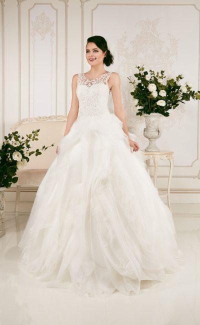 Пышное свадебное платье с кружевным лифом и объемными оборками по многослойному подолу.
