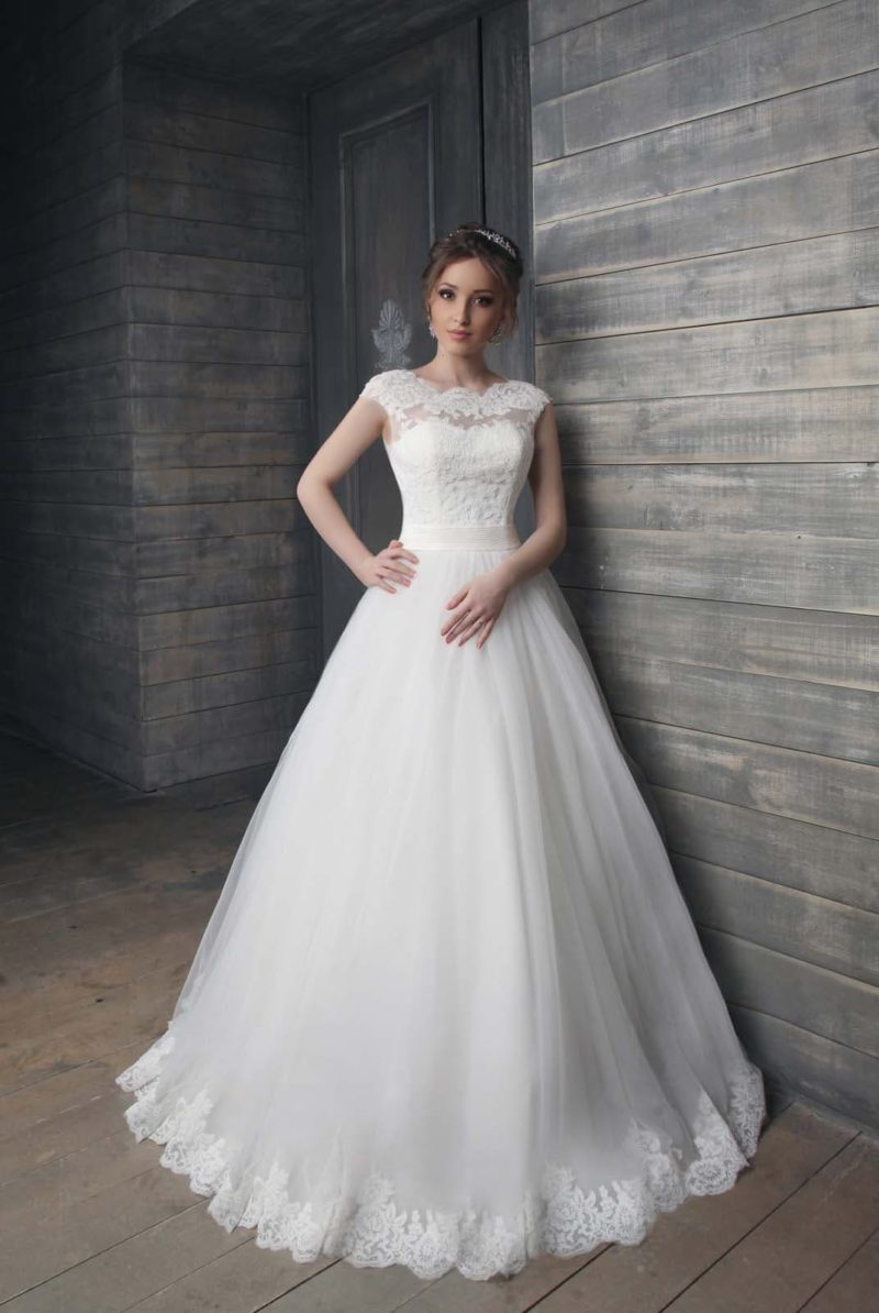 Свадебное платье с широким атласным поясом и кружевным декором закрытого лифа.