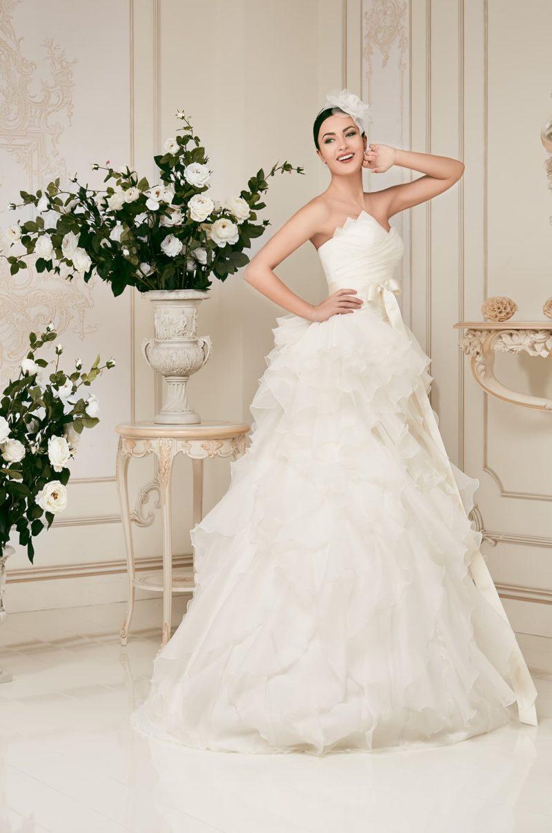 Роскошное свадебное платье с драматичным открытым корсетом и покрытой оборками юбкой.