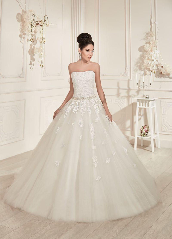 Великолепное свадебное платье с открытым лифом, сияющим поясом и длинным прозрачным шлейфом.
