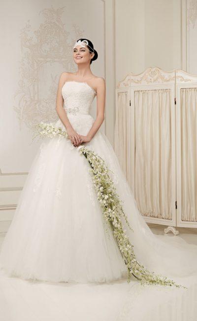 Великолепное свадебное платье с многослойным подолом и открытым лифом, покрытым кружевом.