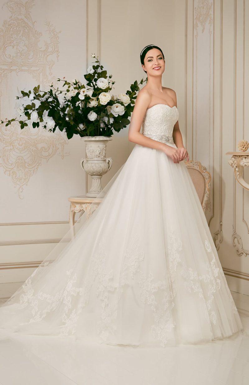 Свадебное платье А-силуэта с кружевным декором юбки и корсета, а также сияющим поясом.