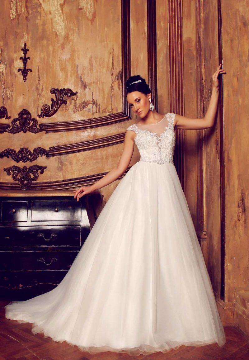 Свадебное платье с глубоким декольте-сердечком, украшенным полупрозрачной вставкой и коротким рукавом.