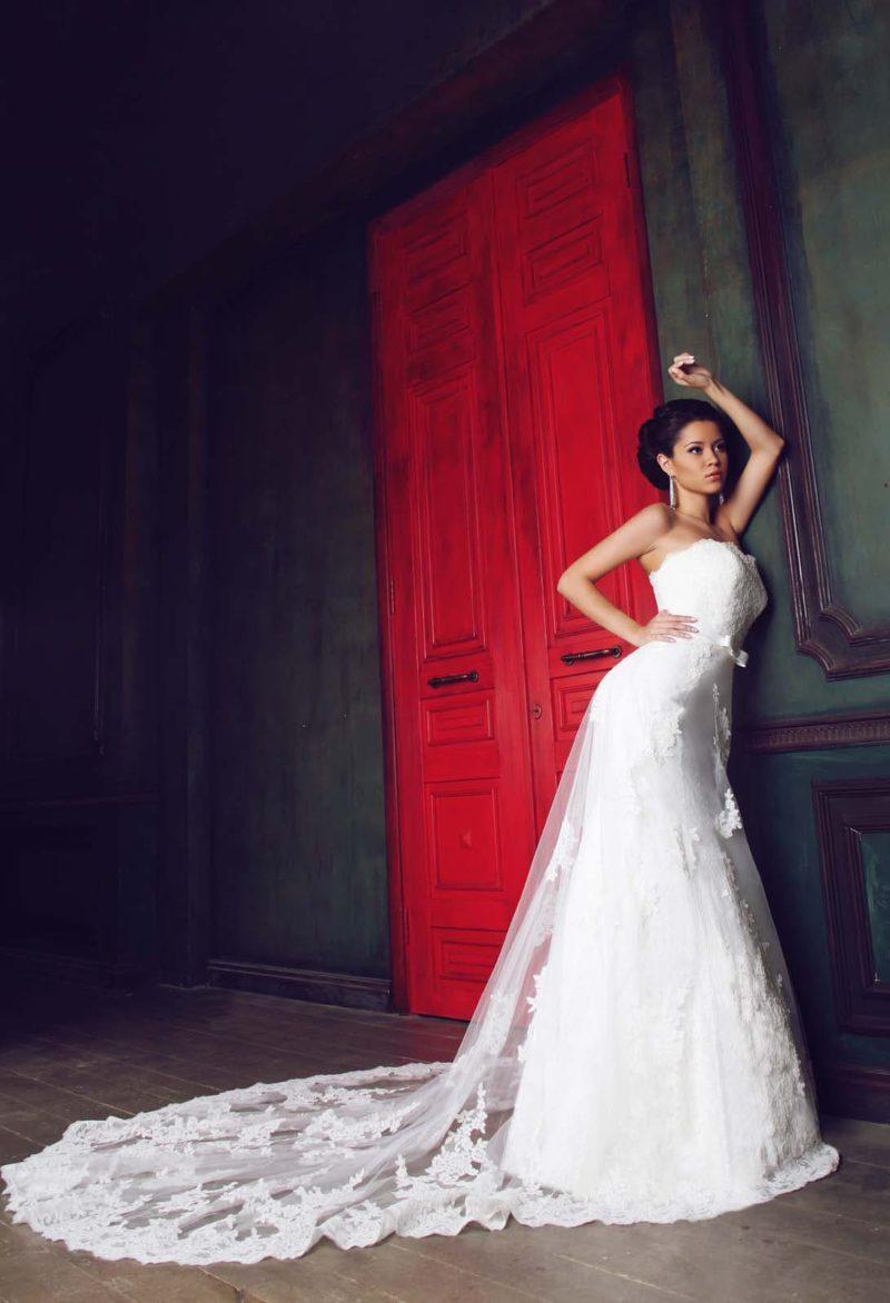 Женственное свадебное платье прямого силуэта с изящным лифом и полупрозрачным длинным шлейфом.