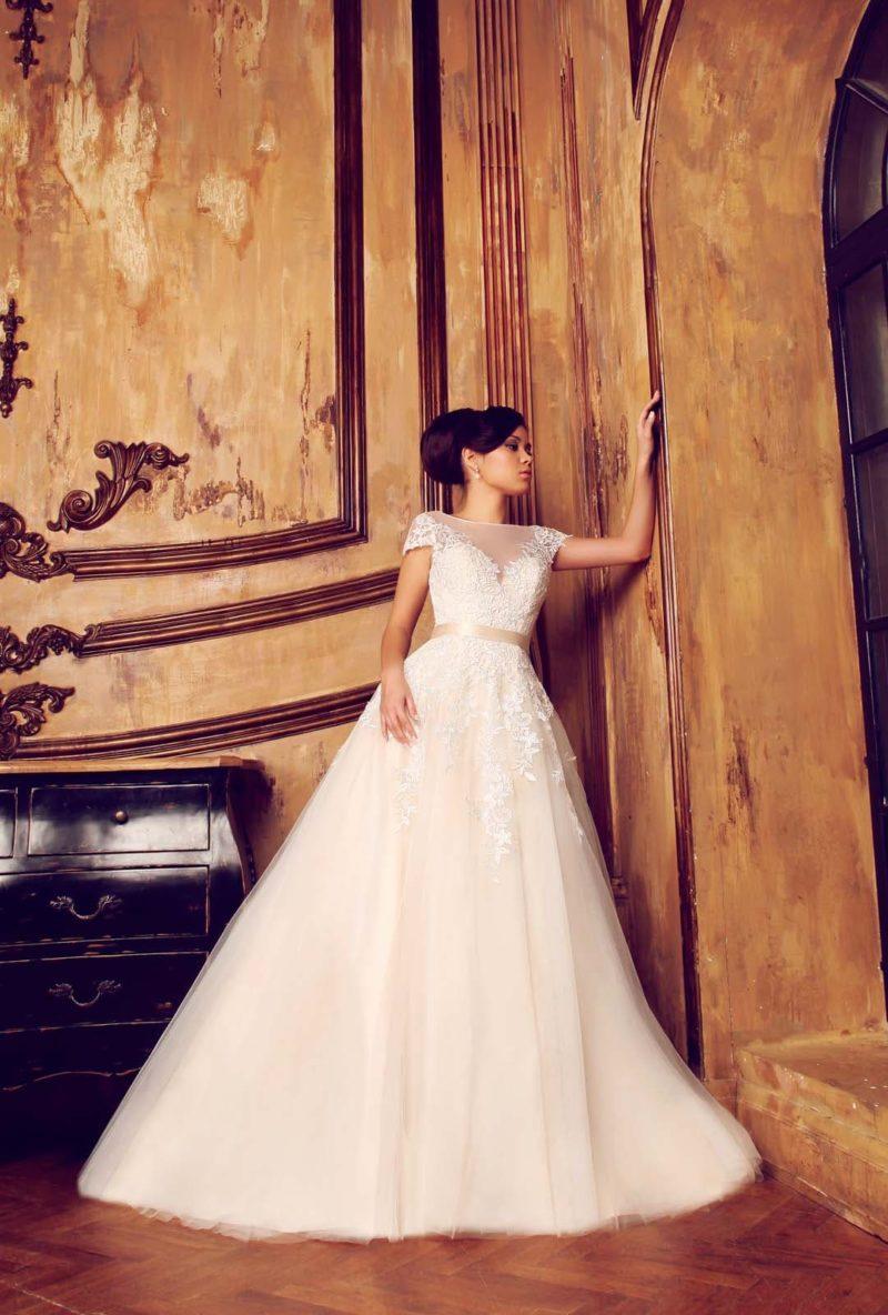 Свадебное платье кремового оттенка, декорированное по корсету белым кружевом и атласным поясом.