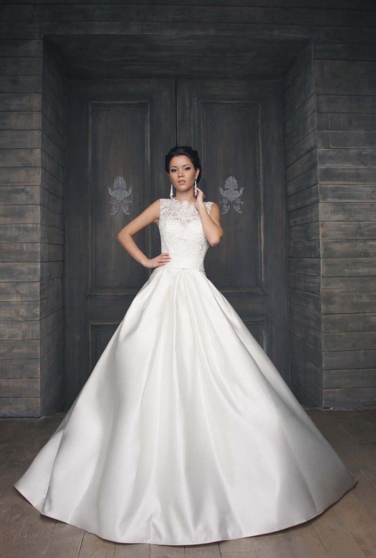Атласное свадебное платье пышного кроя с открытым корсетом, покрытым кружевной тканью.