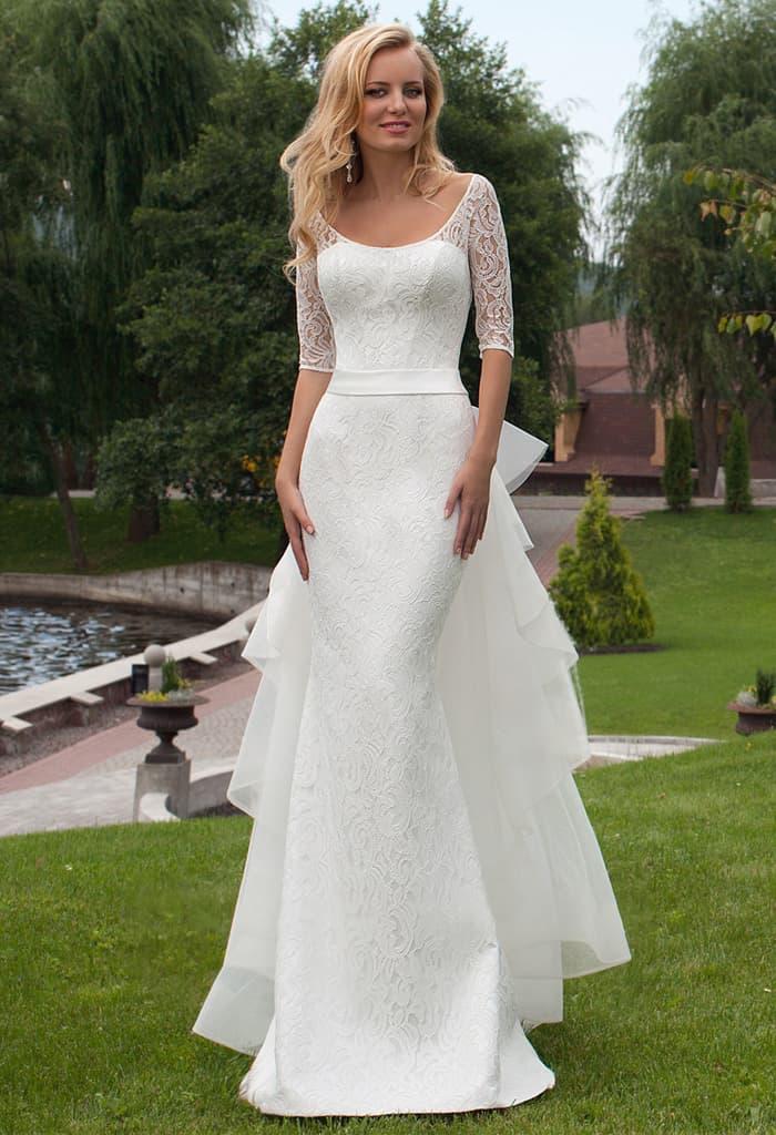 Облегающее свадебное платье с пышным шлейфом сзади и кружевным рукавом до локтя.