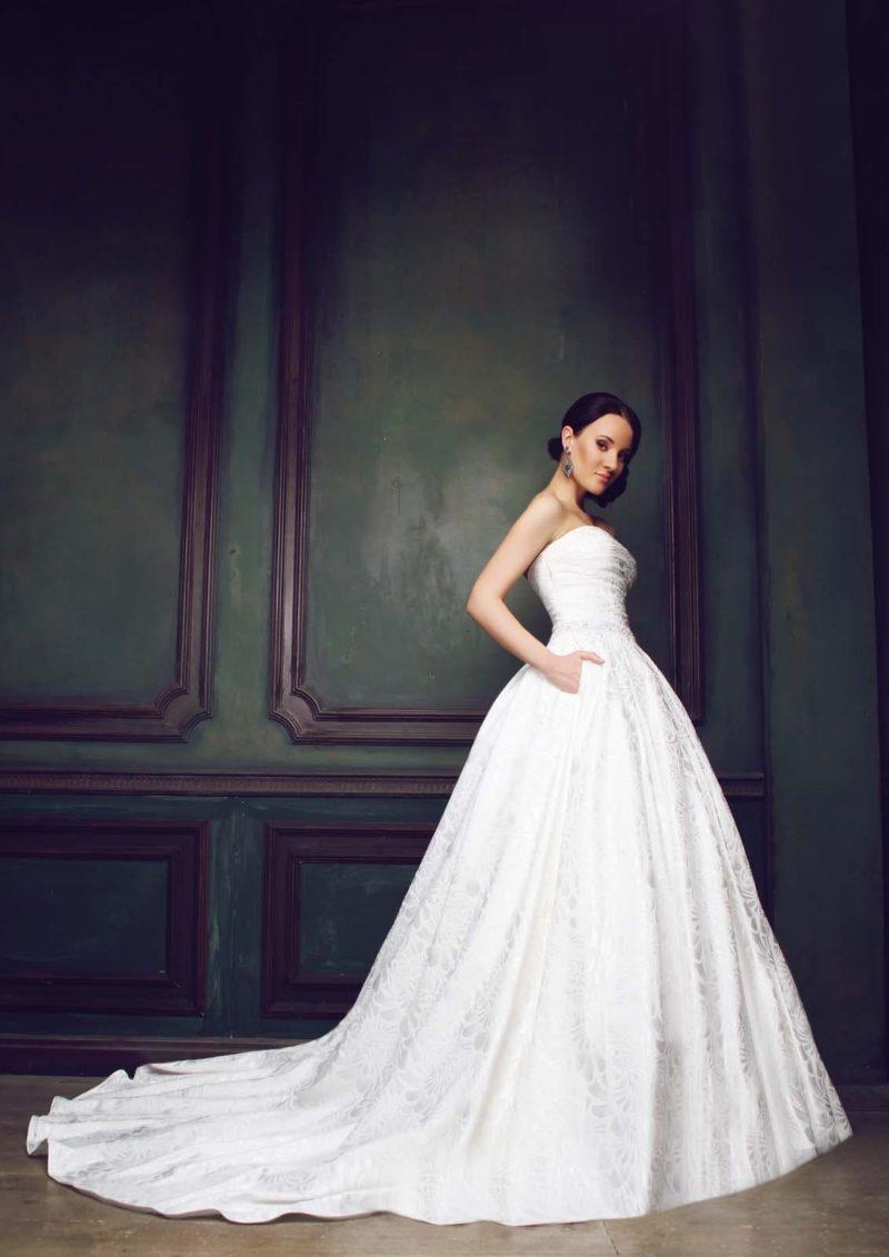 Роскошное свадебное платье открытого кроя и длинным шлейфом, дополняющим пышную юбку.