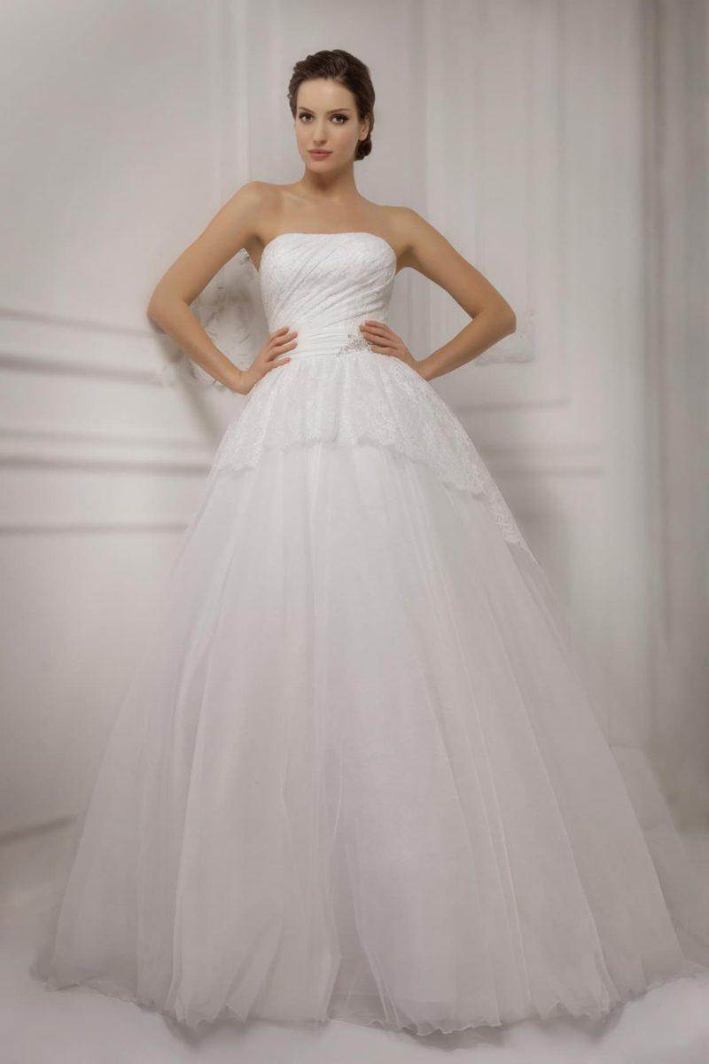 Пышное свадебное платье с необычной кружевной баской и лаконичным открытым лифом.