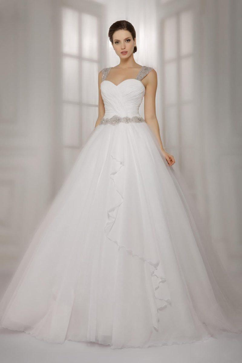 Очаровательное свадебное платье пышного кроя с прозрачными оборками по подолу и сияющими бретелями.