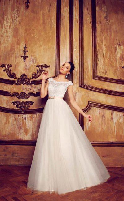 Деликатное свадебное платье с фигурным округлым декольте и узким атласным поясом кремового цвета.