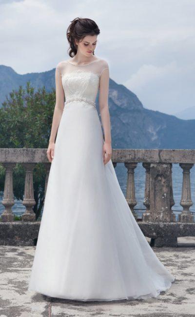 Деликатное свадебное платье с небольшим шлейфом и полупрозрачной тканью по верху.