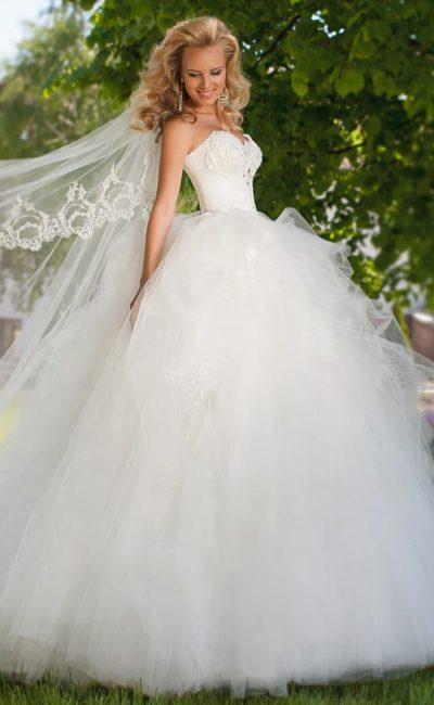 Стильное свадебное платье с глубоким декольте в форме сердца и многослойным подолом.