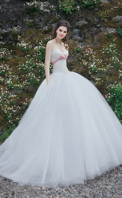 Свадебное платье с завышенной линией талии, выделенной розовым поясом, и пышной юбкой.