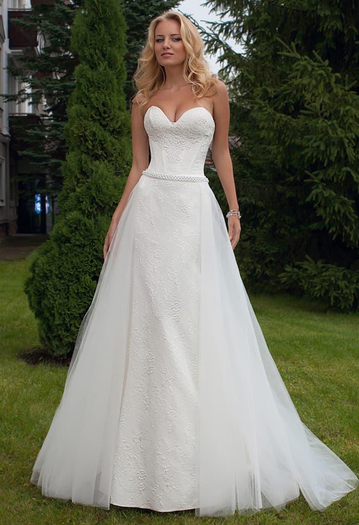 Свадебное платье с соблазнительным декольте и пышной отделкой юбки.