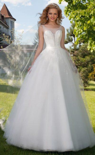 Закрытое свадебное платье с кружевным декором верха подола и глубоким декольте, покрытым тонкой вставкой.