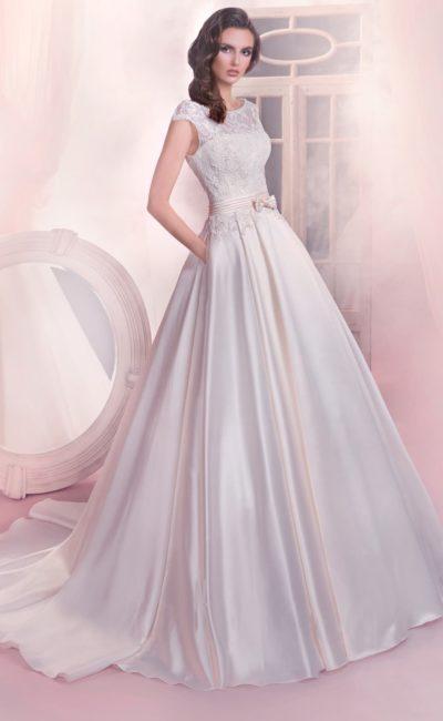 Пышное свадебное платье с атласной юбкой и кружевной отделкой закрытого верха с коротким рукавом.