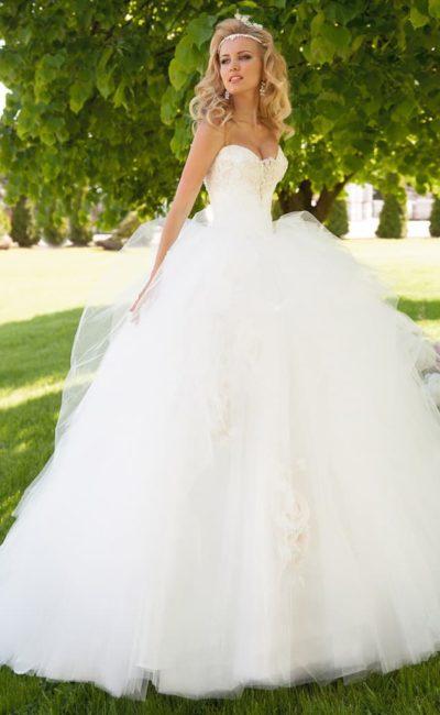 Романтичное свадебное платье пышного кроя с открытым корсетом, украшенным аппликациями.