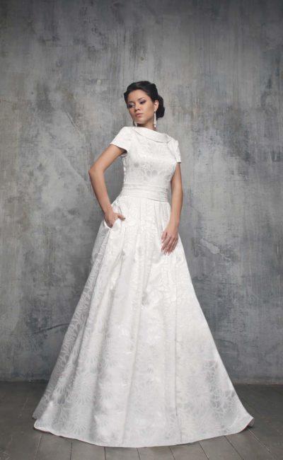 Свадебное платье из фактурной ткани с V-образным вырезом на спинке и округлым декольте на лифе.