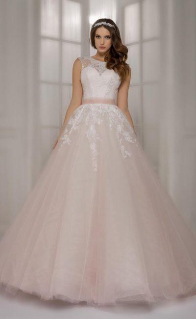 Пышное свадебное платье с объемным подолом кремового оттенка и широким атласным поясом.