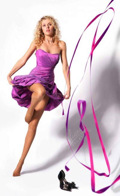 Фиолетовое вечернее платье из фактурной ткани, украшенной драпировками.
