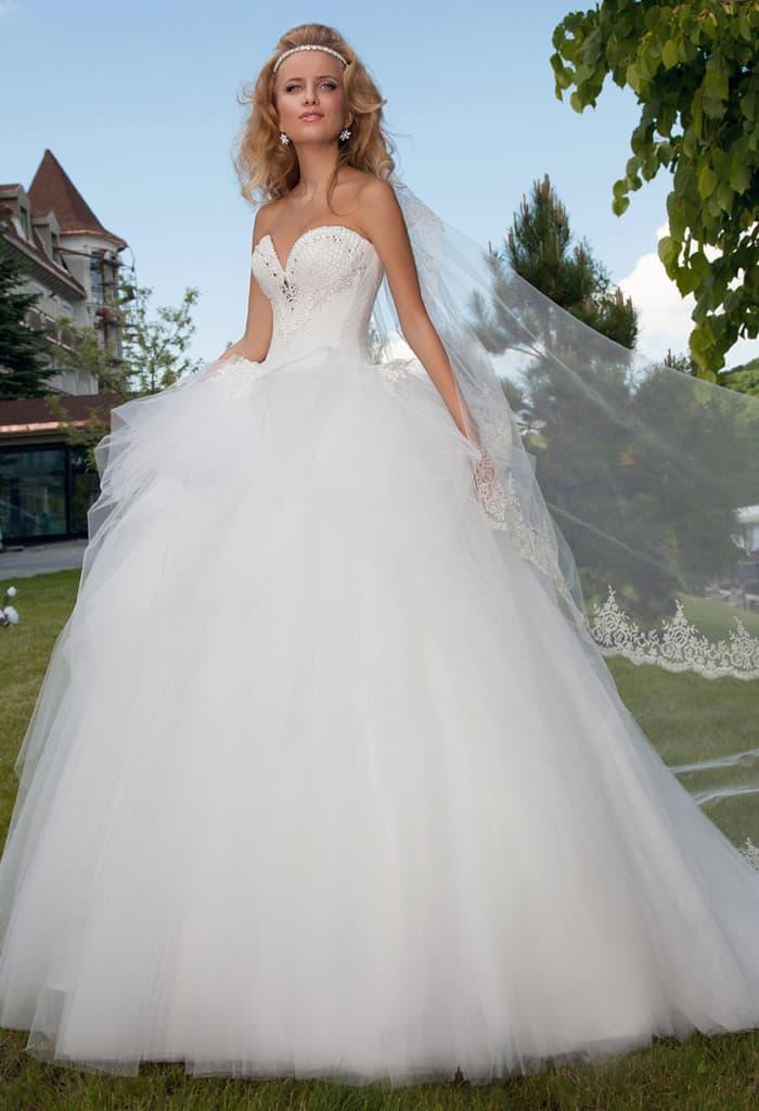 Кокетливое свадебное платье с многослойной пышной баской и глубоким вырезом в форме сердца.