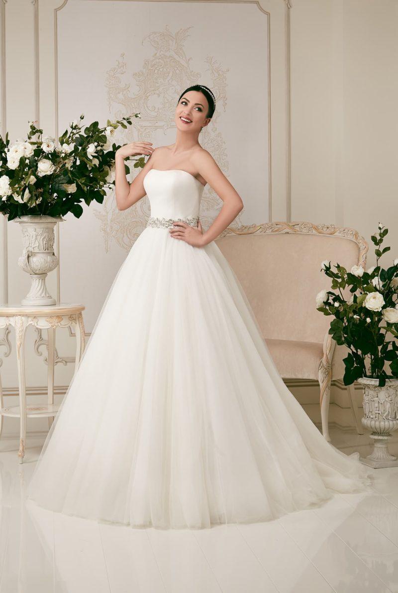 Лаконичное свадебное платье с открытым лифом и сверкающей вышивкой по сияющему поясу.