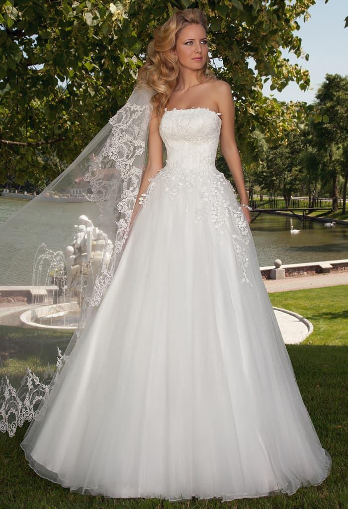 Пышное свадебное платье с лифом прямого кроя и кружевным декором.