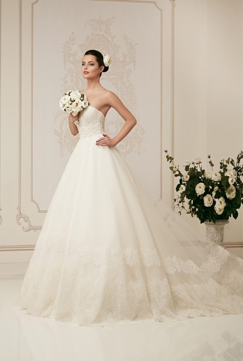 Свадебное платье с открытым лифом, дополненным кружевным болеро, и пышной юбкой.