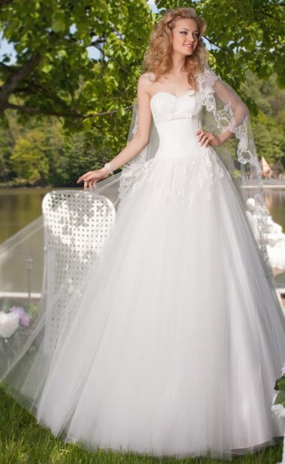 Открытое свадебное платье с лифом в форме сердца и лаконичной многослойной юбкой.