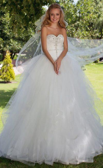 Торжественное свадебное платье с бисерной вышивкой по корсету и сложного кроя пышной юбкой.