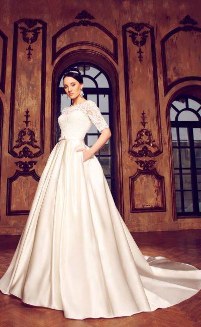 Атласное свадебное платье со скрытыми карманами и кружевным декором верха с длинным рукавом.