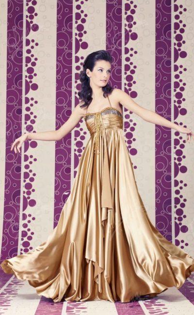Золотое вечернее платье с изящным открытым лифом с тонкими бретелями.