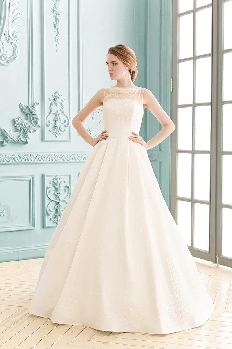 Атласное свадебное платье с элегантной юбкой и кружевным декором над открытым корсетом.