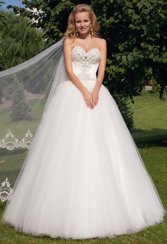 Свадебное платье с открытым лифом, украшенным вышивкой, и воздушным подолом.