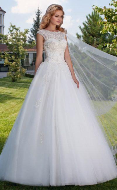 Пышное свадебное платье с кружевной отделкой верха и вырезом «замочная скважина» сзади.