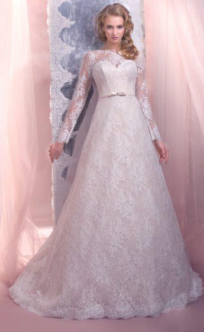 Пышное свадебное платье с вырезом в форме сердца, укрытым кружевной тканью, создающей длинные рукава.