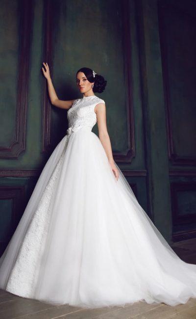 Свадебное платье с высоким вырезом под горло и роскошной многослойной юбкой.