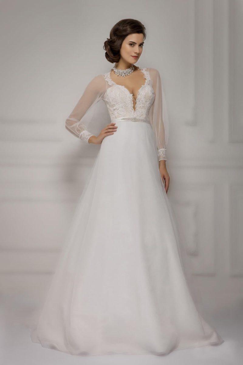 Закрытое свадебное платье с полупрозрачными рукавами и кружевным глубоким вырезом.