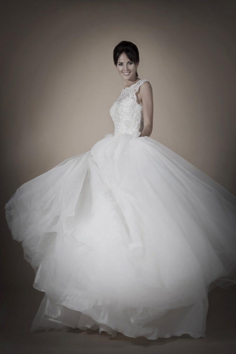 Роскошное свадебное платье с лаконичной многослойной юбкой, вырезом на спинке и изящным лифом.