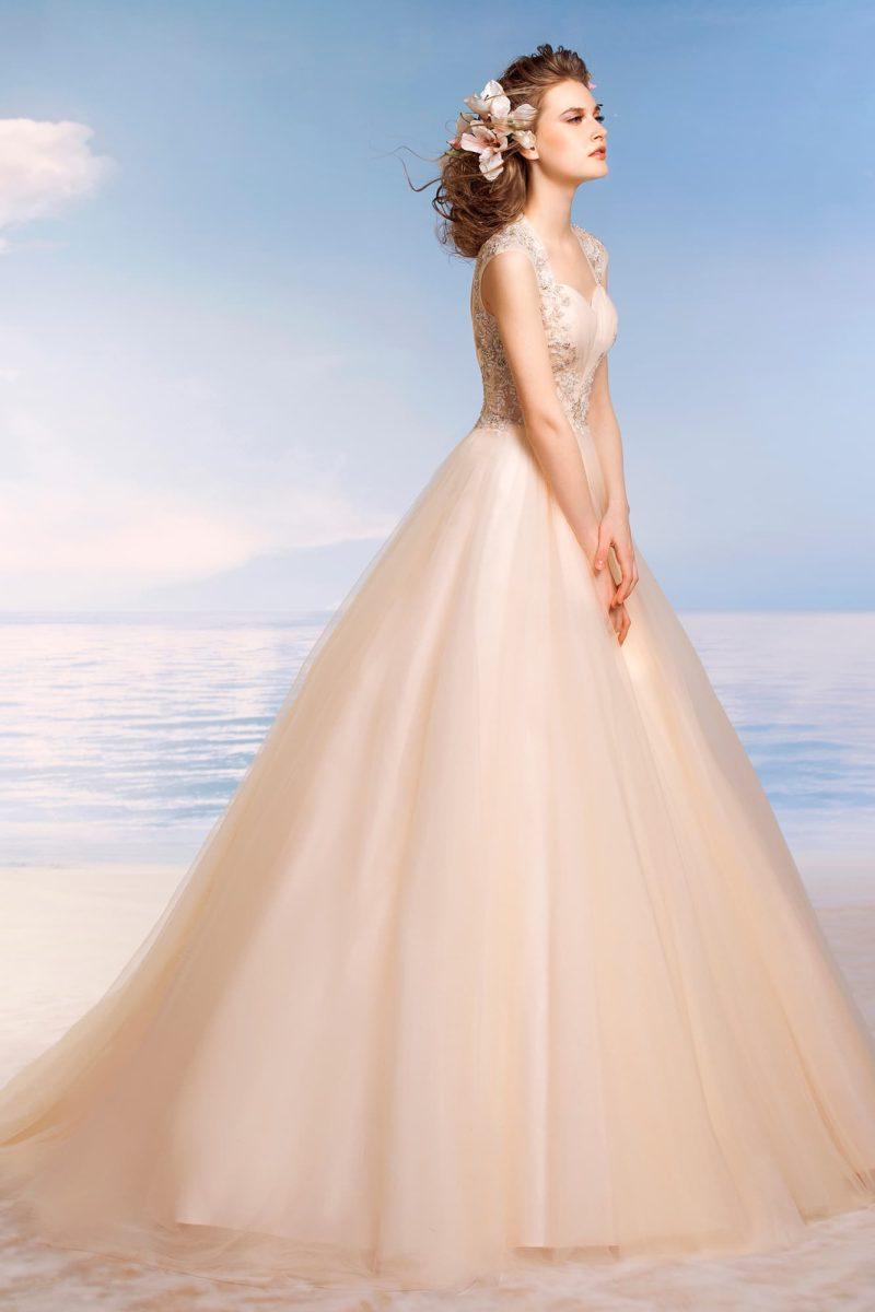 Кремовое свадебное платье пышного кроя с сияющей бисерной вышивкой по бокам корсета и лифу.